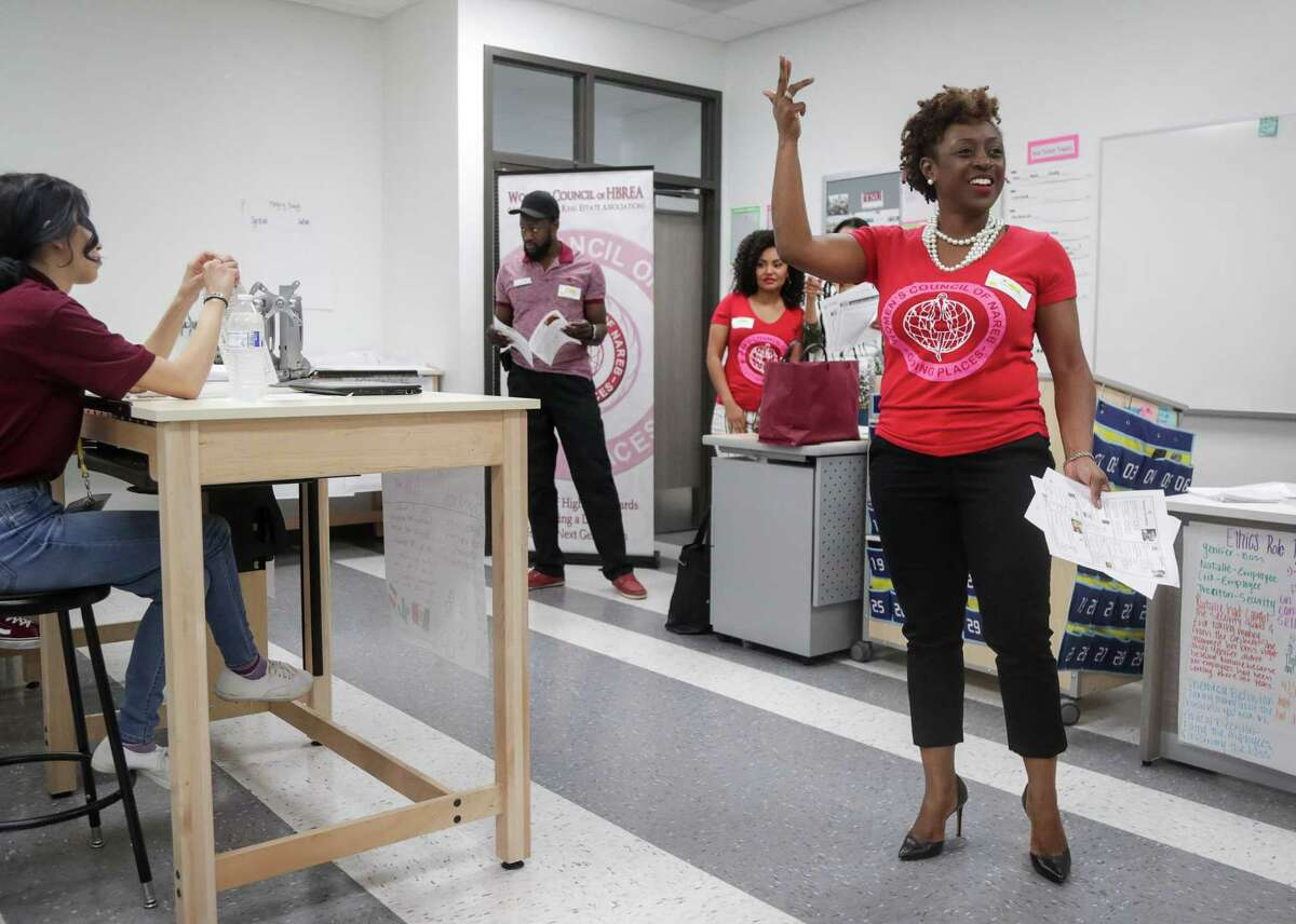 LaTisha Grant, right, president of the Women's Council of the Houston Black Real Estate Association, talks to students at Wisdom High School about financial literacy on Wednesday, April 10, 2019, in Houston.