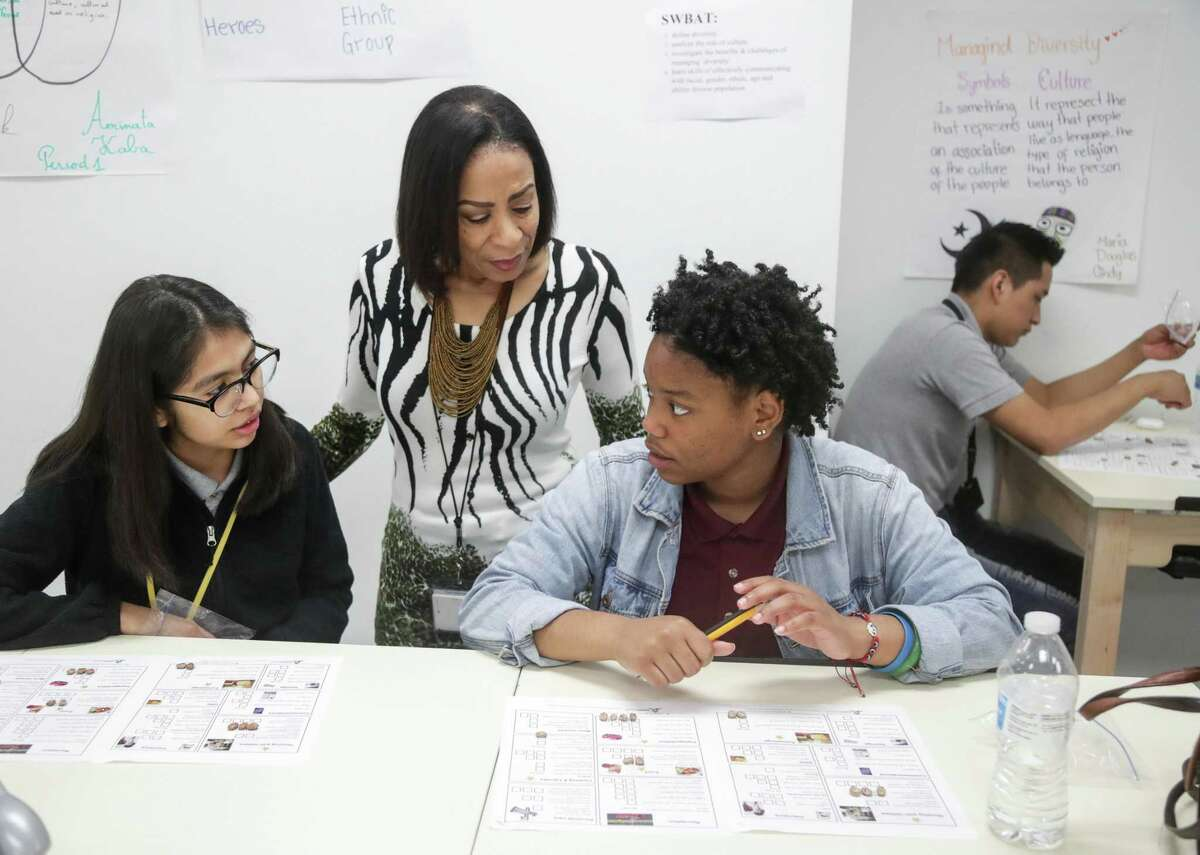 Gaylyn Smith, second from left, a teacher of 17 years in HISD, helps her students Maria Rios, left, 17, and Eyanni Waterman, 17, with a budgeting exercise during her global business class, as Alvaro Calel, right, works on the same exercise, at Wisdom High School on Wednesday, April 10, 2019, in Houston. A group from the Houston Black Real Estate Association visited the class to help teach students about financial literacy.