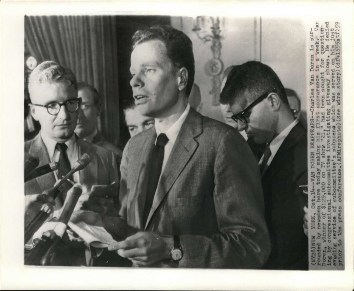 """New York: Arraigned on Perjury Charges, Charles Van Doren is surrounded by newsmen here today making his first appearance in a week. Van Doren, winner of $129,000 on TV show """"Twenty-One,"""" had been sought for questioning by congressional subcommittee investigation giveaway shows. He denied evading service of subcommittee's subpoena which was served on him just prior to the press conference."""