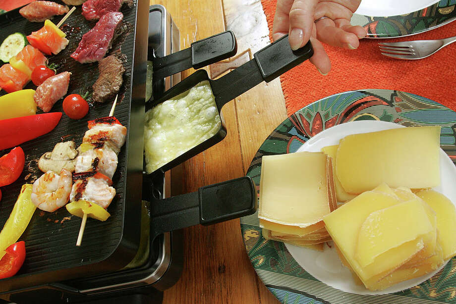 The restaurant's hallmark dishes are shareable, Raclette-topped Swiss meals. Guests can melt their own Raclette cheese in pans at a table grill and then scrape the cheese over dishes like potatoes, vegetables, fruit and meats. Guests are also given the option of Raclette cheese melted from a half wheel scraped over their dish of choice tableside. Photo: Bernard Weil/Toronto Star Via Getty Images