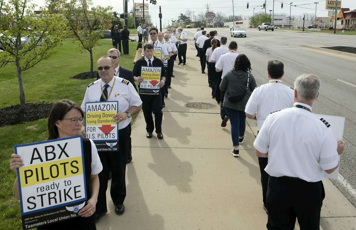 Beth Mayer, an ABX Air pilot, bottom left, walks with other Teamster Local Union No. 1224 members in an informational picket to raise concerns about stalled contract negotiations and operation concerns at ATSG holding companies subsidiaries and Atlas Air World Wide Holdings on Thursday April 11, 2019, in Florence, Ky. (Albert Cesare/The Cincinnati Enquirer via AP)