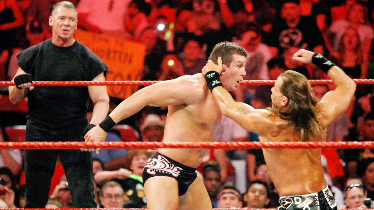 (L-R) World Wrestling Entertainment Inc. Chairman Vince McMahon watches as wrestlers Ted DiBiase and Shawn Michaels compete during the WWE Monday Night Raw show at the Thomas & Mack Center August 24, 2009 in Las Vegas, Nevada.