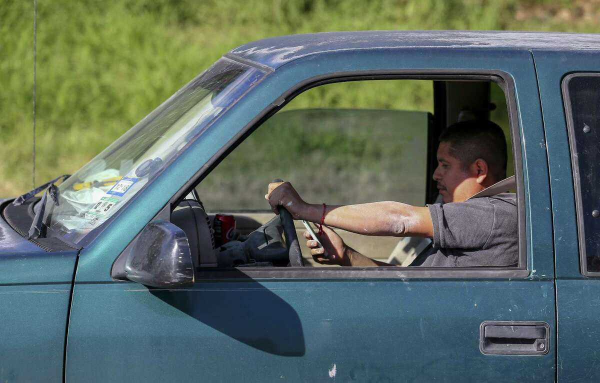 A motorist uses a cell phone while driving on the westbound lanes of Interstate 10 near Loop 610 on Oct. 29, 2018.