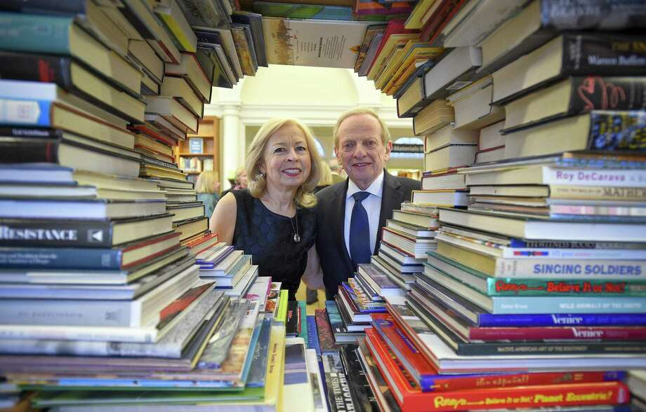 """Mary Sommer and Jay Sandak are framed in an arrangement of books. Both were honored at Ferguson Library's spring fundraiser """"A Novel Affair"""" on Thursday, April 11, 2019 for their longstanding commitment to the library and the Stamford community. Photo: Matthew Brown / Hearst Connecticut Media / Stamford Advocate"""