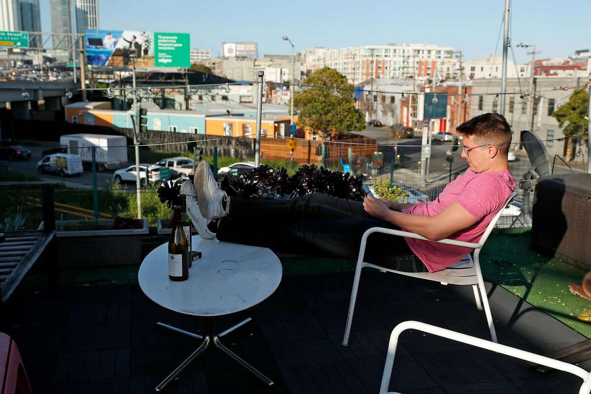 Mike Sizemore relaxes on the deck of his 5th Street residence across the street from the Bryant Navigation Center on Bryant Street in San Francisco, Calif., on Wednesday, April 10, 2019.