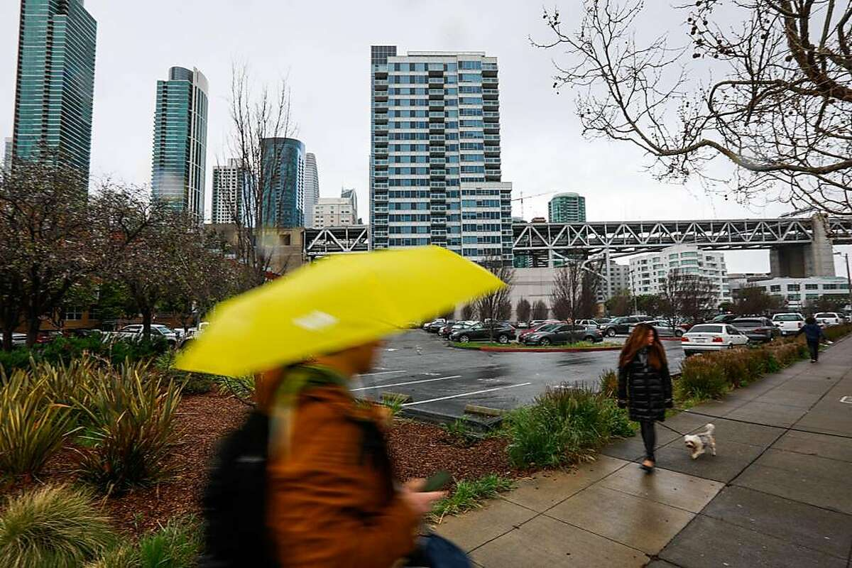 People pass by the Watermark apartment complex which is situated next to a parking lot that is being proposed by Mayor London Breed to become a Navigation Center in San Francisco, California, on Wednesday, March 27, 2019.