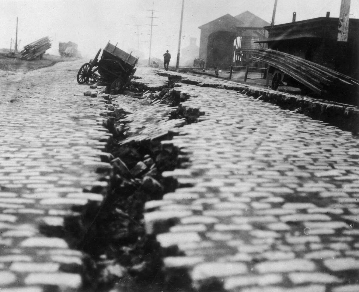 1906: View of a cobblestone street, which was split down the middle after the Great Earthquake in San Francisco, California. A wooden cart has fallen into the crack. ~~