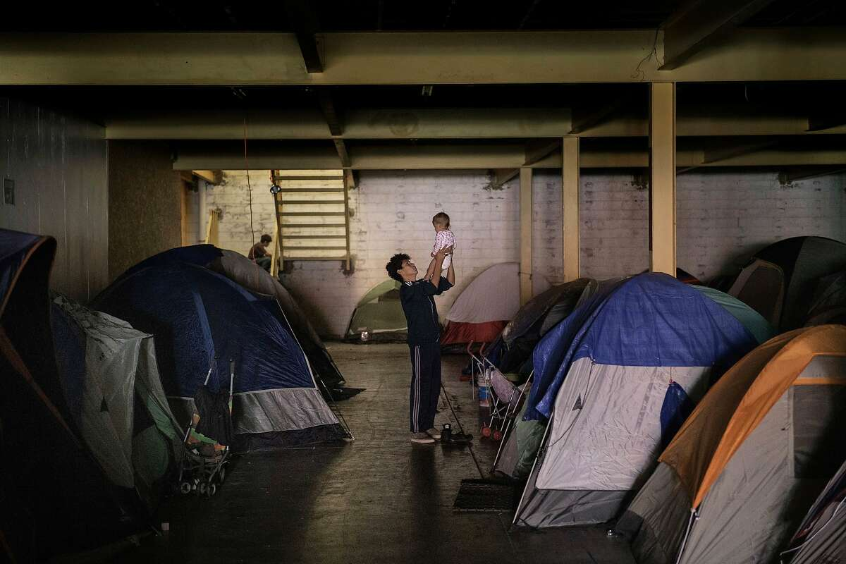 """A man from Honduras holds a baby inside an empty warehouse used as a shelter set up for migrants in downtown Tijuana, Mexico, Tuesday, Dec. 25, 2018. Critics, including former allies and some of the migrants themselves, say Pueblo Sin Fronteras, a group of activists escorting the caravan called in English, """"People Without Borders,"""" downplayed the dangers of Central Americans' treks toward the United States, especially for families and small children, and misled the participants about how long they would have to wait on the Mexican side to apply for asylum. (AP Photo/Daniel Ochoa de Olza)"""