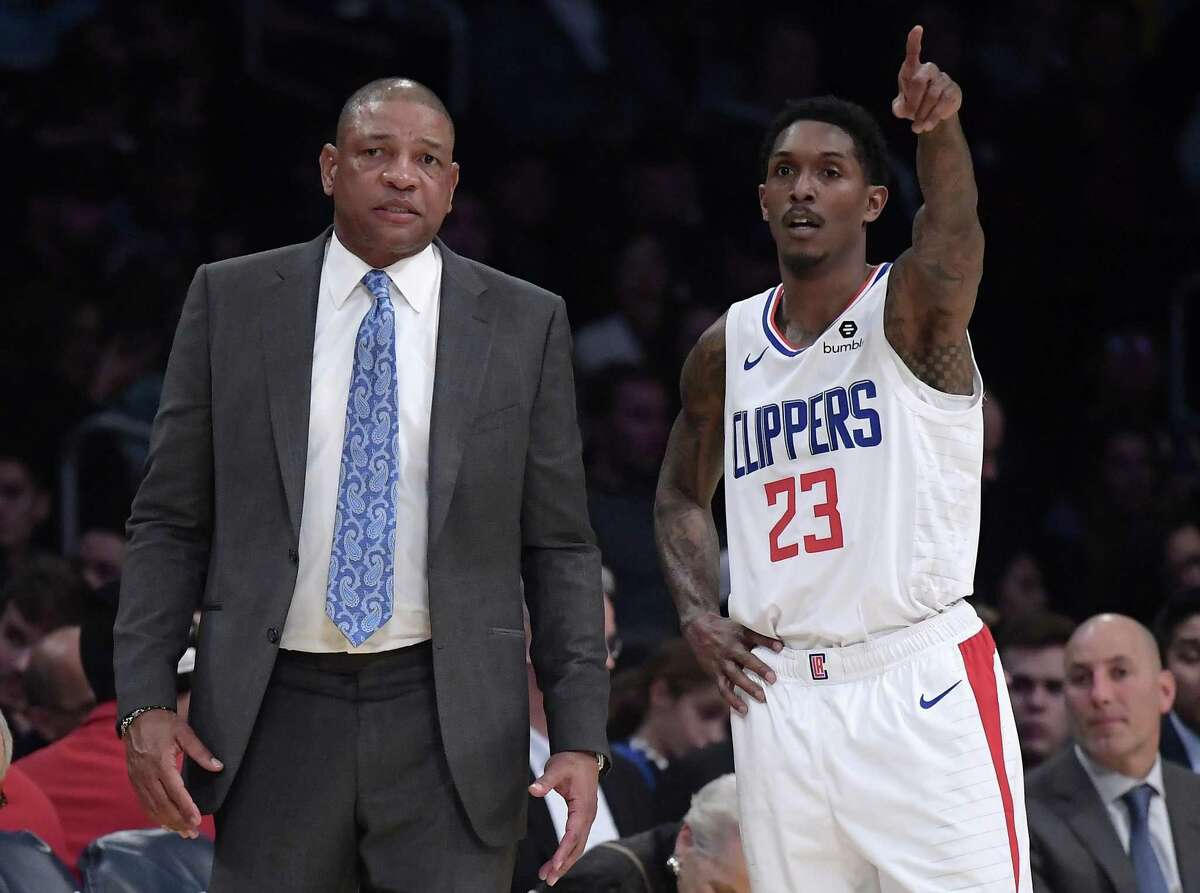 Los Angeles Clippers coach Doc Rivers, left, and guard Lou Williams talks during the second half of the team's NBA basketball game against the Los Angeles Lakers on Friday, Dec. 28, 2018, in Los Angeles. The Clippers won 118-107.