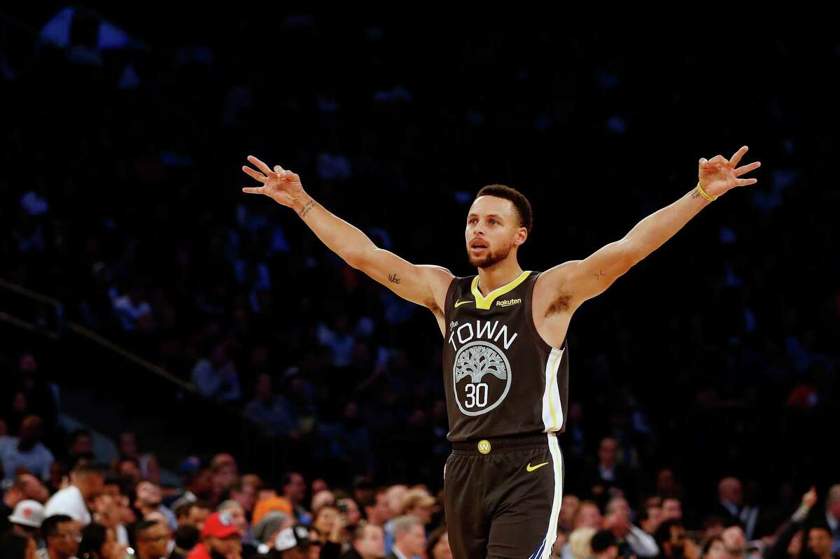Stephen Curry #30 of the Golden State Warriors celebrates after teammate Alfonzo McKinnie #28 hits a three point basket against the New York Knicks during the fourth quarter at Madison Square Garden on October 26, 2018 in New York City.