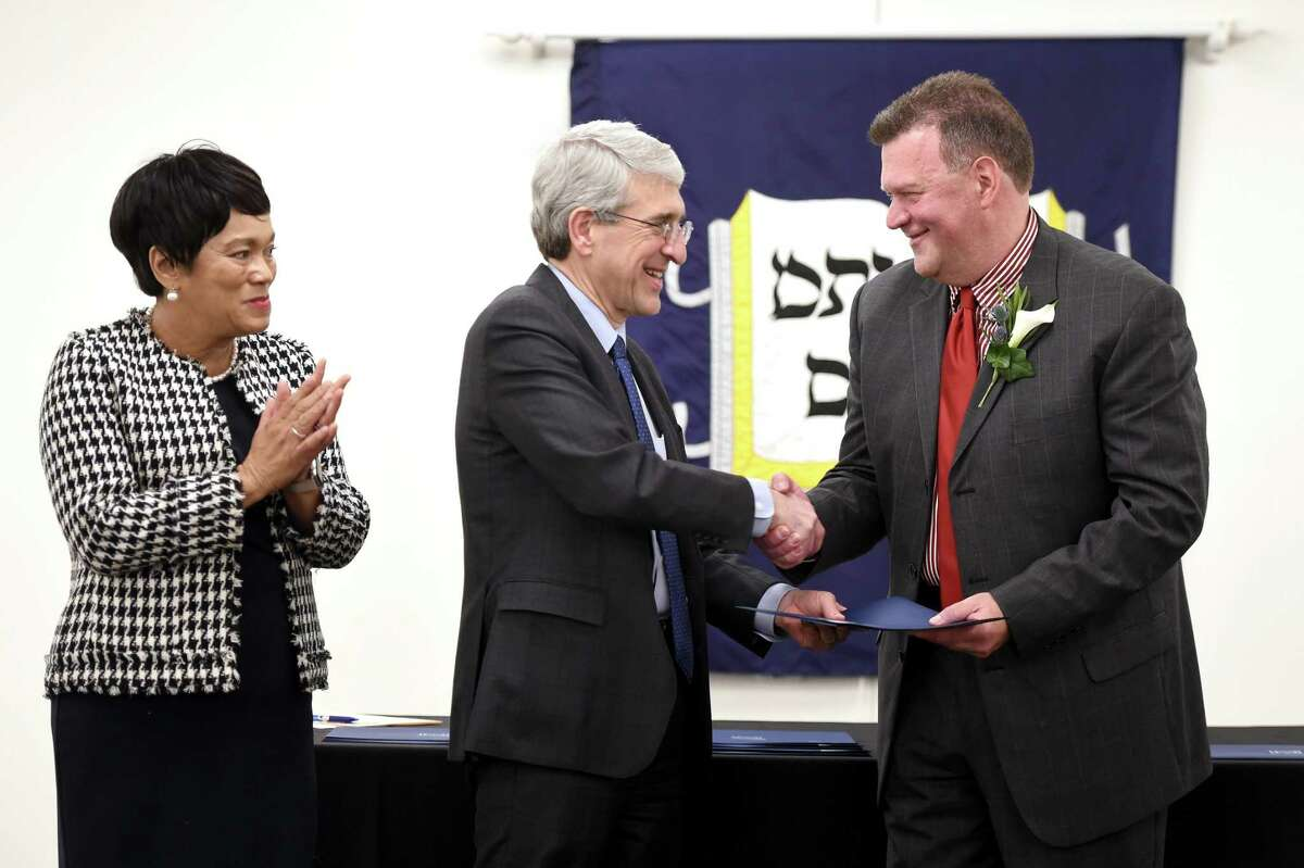 From left, Harp, applauds as Salovey congratulates David Greco, co-founder and director of Arte Inc., during the Yale Seton Elm-Ivy Awards Thursday. Arte Inc. is dedicated to developing and promoting Latino art, culture and education.