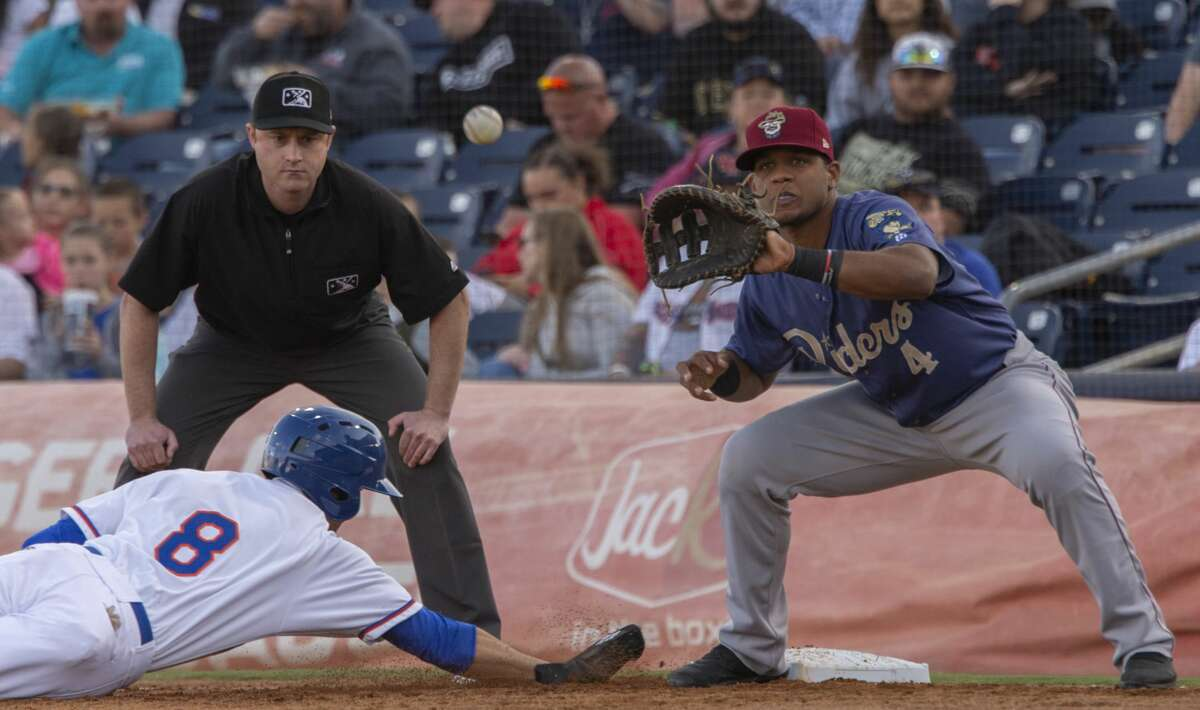 RockHounds' Luke Persico dives back to first to beat the throw 04/11/19 Frisco's Andretty Coredro waits on the ball at the home opener at Security Bank Ballpark. Tim Fischer/Reporter-Telegram