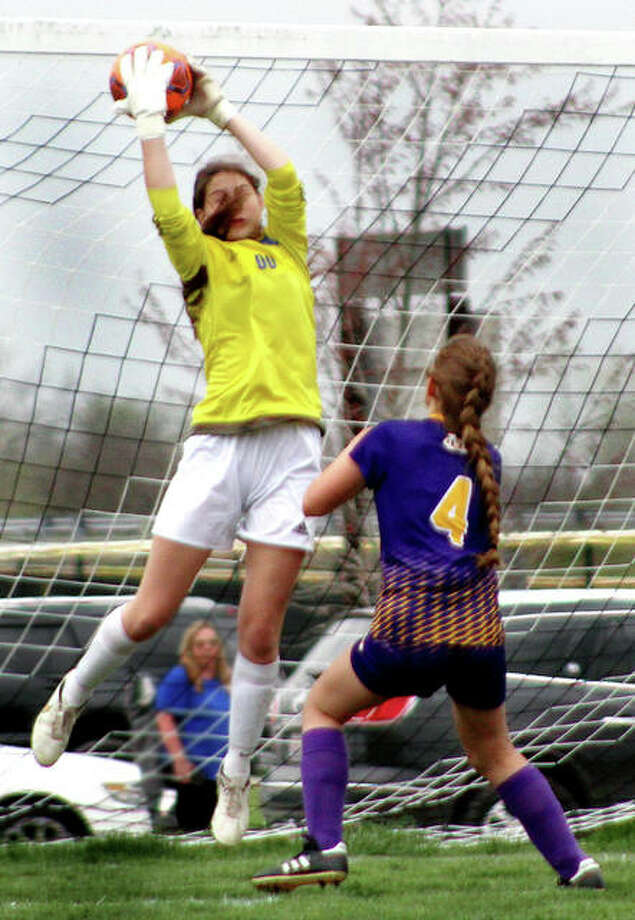 Marquette goalie Claire Rodgers goes high to snare the ball as Civic Memorial's Emily Smith (4) closes in Thursday at the Bethalto Sports Complex Photo: Pete Hayes | The Telegraph
