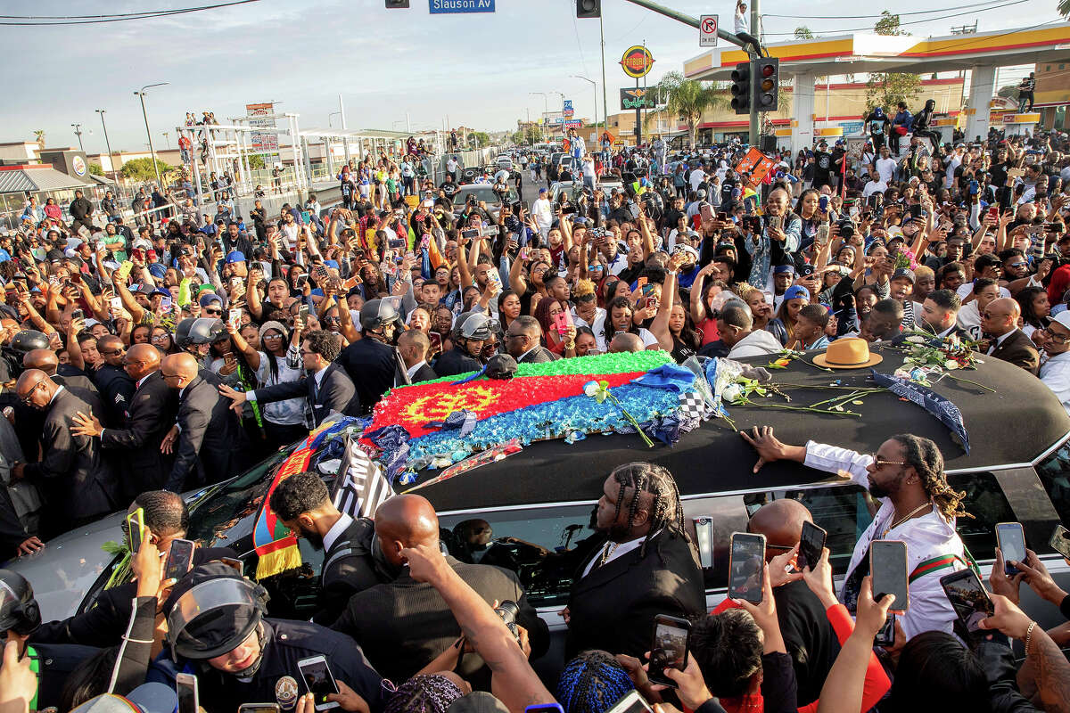Nipsey Hussle's procession passes his Marathon Clothing store after his memorial at the Staples Center in Los Angeles, California, on April 11, 2019. - The Grammy-nominated artist was killed in front of The Marathon Clothing store he founded in 2017.