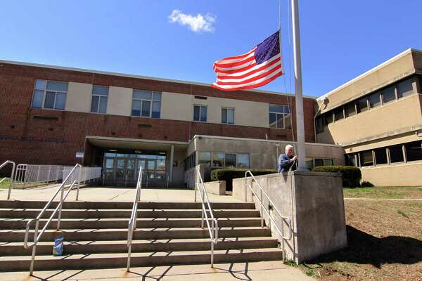 Brian Turner retires the flag in front of Ansonia Middle School on Howard Ave in Ansonia, Conn., on Thursday April 11, 2019. This school, which started as the city's high school, opened in 1937. Due to many needed repairs and upgrades, the Ansonia the BOE wants to build a new middle school on Pulaski Highway next to the current high school.
