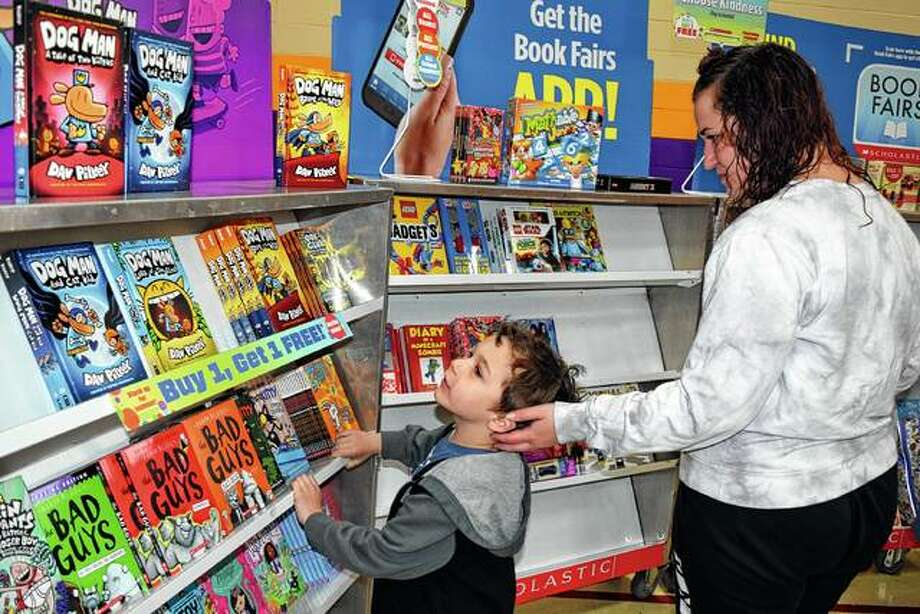 Sebastian Watkins, 4, and Chelsea Watkins of Jacksonville consider the options at a book fair Thursday at Eisenhower Elementary School. Photo: Samantha McDaniel-Ogletree | Journal-Courier