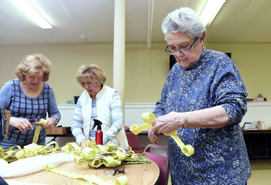 In New Haven, from left, Therese Incarnato of New Haven, Mary Florenzano of New Haven and Mary Quinlan of East Haven assemble palm crosses for Palm Sunday in the basement of St. Michael Church April 11, 2019. This is the third year that volunteers under the direction of Jean Quartiano have made palm crosses for parishioners of the church. Photo: Arnold Gold / Hearst Connecticut Media / New Haven Register