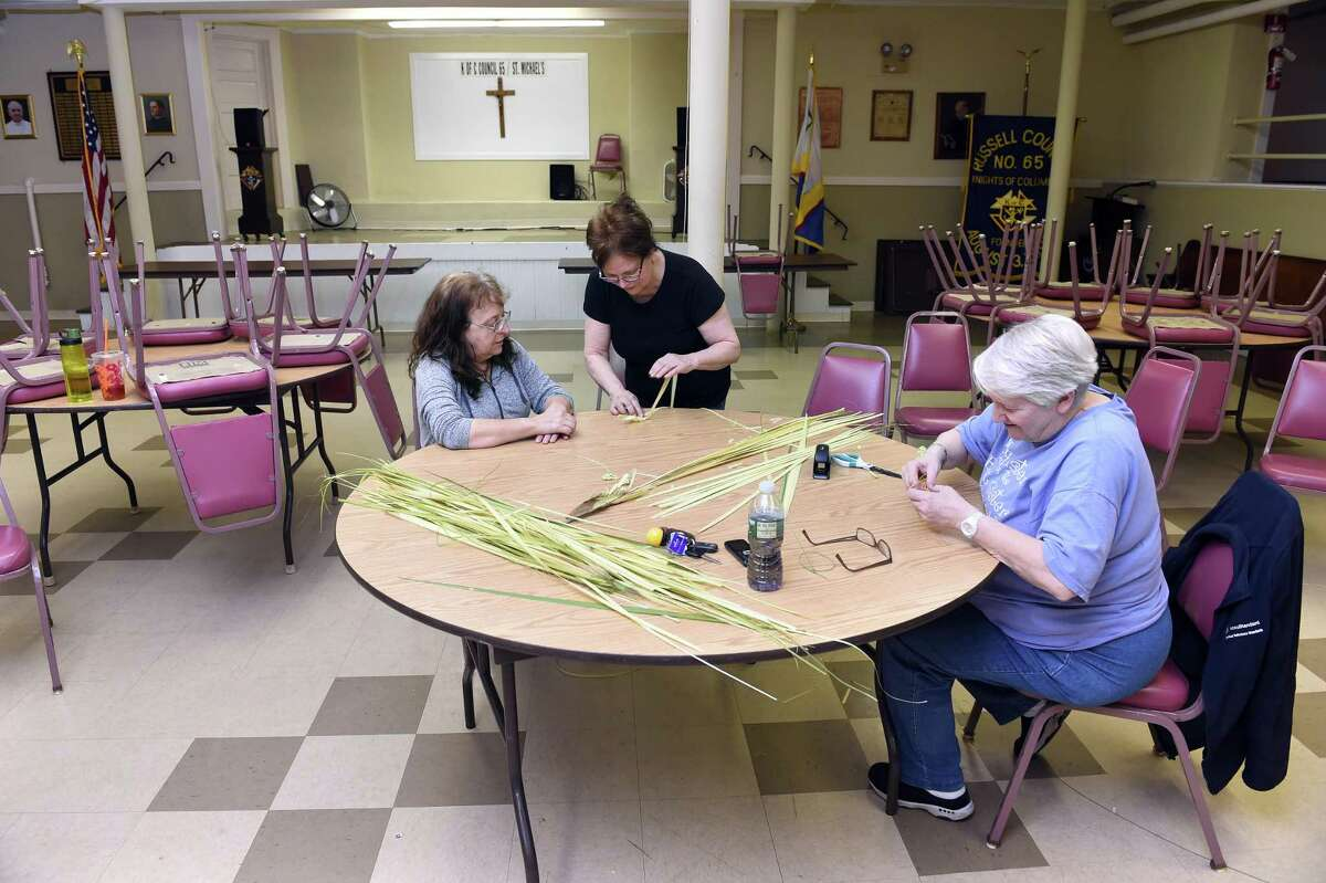 In New Haven, from left, Kathy Heimann of West Haven gets instructions from Peggy Cummings of East Haven for making palm crosses as Kathy Vissicchio of East Haven works on others in the basement of St. Michael Church in New Haven on April 11, 2019. This is the third year that volunteers under the direction of Jean Quartiano have made palm crosses for parishioners of the church for Palm Sunday.
