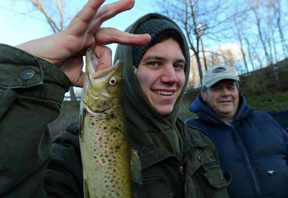 Norwalk residents Anthony Russo and his father Bob Russo display a trout they caught while fishing on the Norwalk River during opening day Saturday, April 8, 2017, in Wilton, Conn. The 2019 trout season opens Saturday. Photo: Erik Trautmann / Hearst Connecticut Media / Norwalk Hour