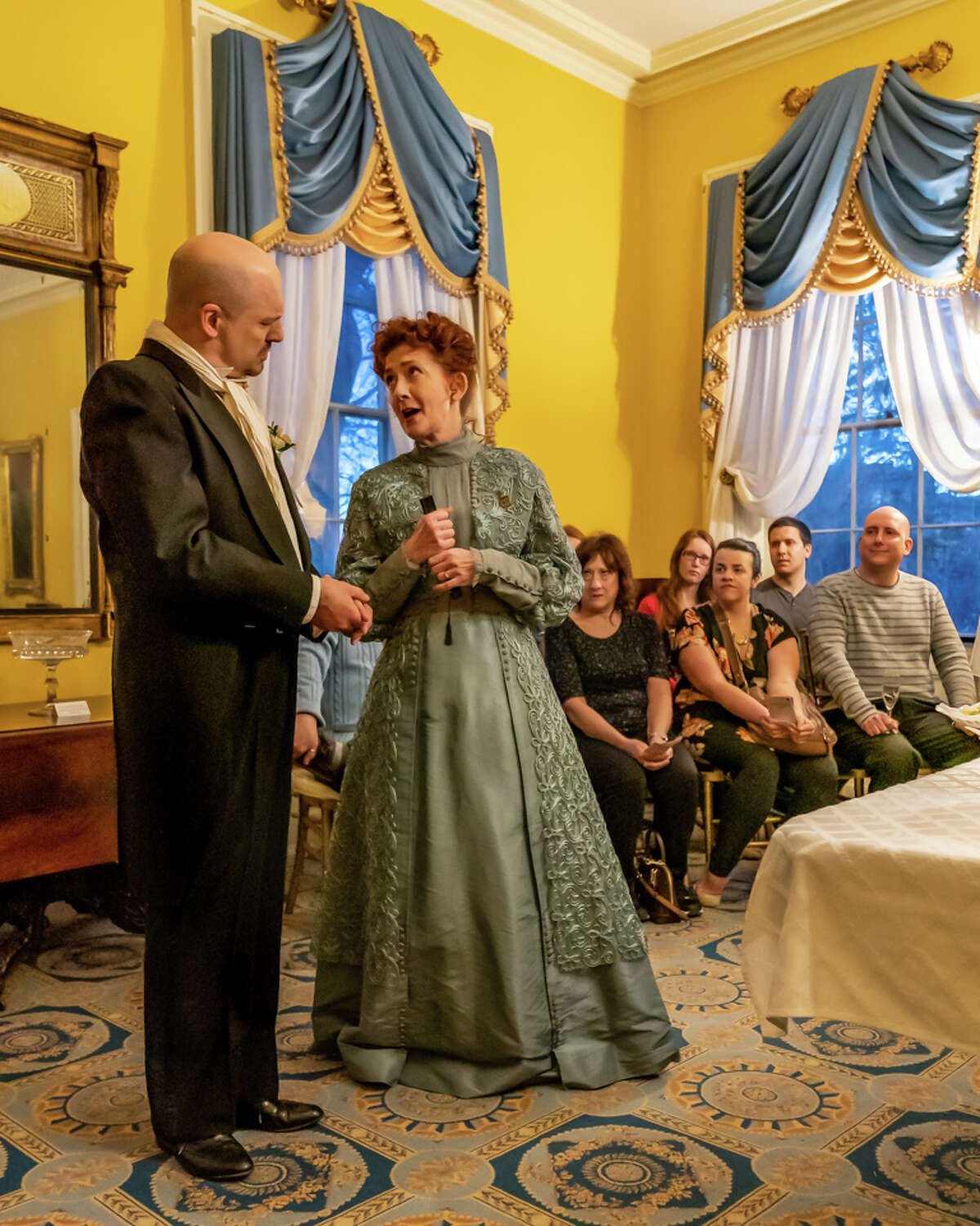 """Tony Pallone, left, and Janet Hurley Kimlicko are antagonists in the NorthEast Theatre Ensemble production of Oscar Wilde's """"An Ideal Husband,"""" running through April 28, 2019, at Ten Broeck Mansion in Albany.Audience members are in the background."""