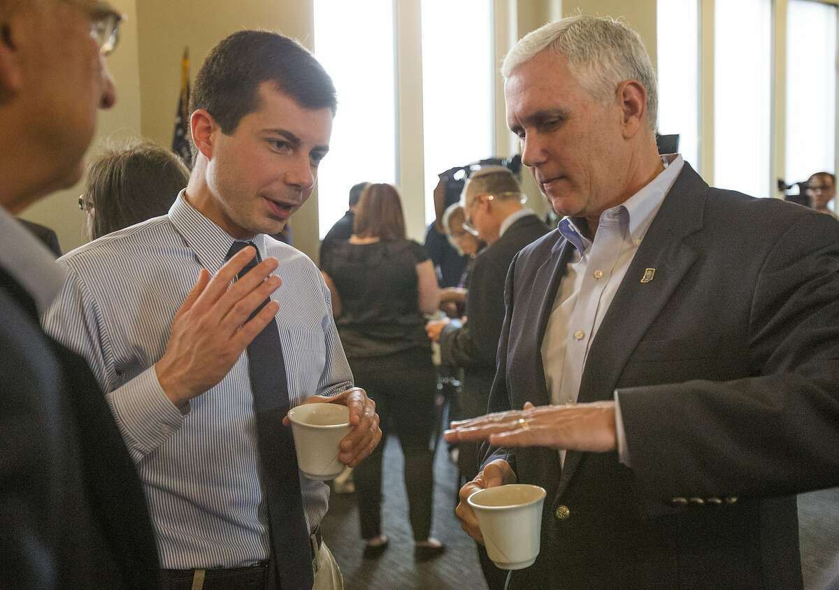 FILE - In this May 1, 2015, file photo, then-Indiana Gov. Mike Pence, right, talks with South Bend Mayor Pete Buttigieg during a visit to recap the legislative session that ends in South Bend. Democratic presidential candidate Pete Buttigieg blasts Vice President Mike Pence's religious conservatism. But as the mayor of South Bend, Indiana, his tone toward the state's former governor was more muted. The two once had a cordial relationship. (Robert Franklin/South Bend Tribune via AP)