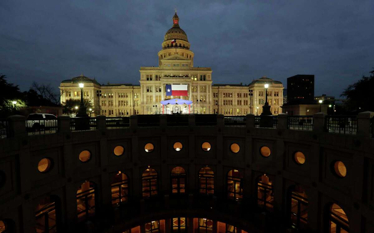 A large Texas flag hangs from the Texas State Capitol as workers prepare the grounds for Tuesday's Inauguration Ceremonies, in Austin on Monday, Jan. 14, 2019.