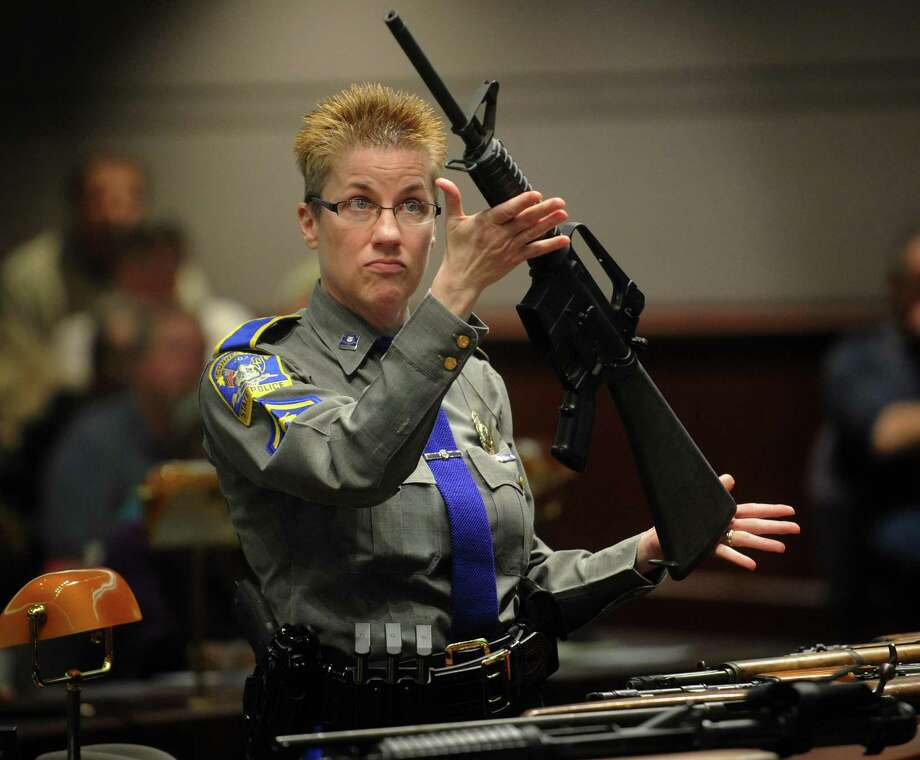 State police Detective Barbara Mattson displays a Bushmaster assault-style rifle, the type used in the Sandy Hook School shooting, during testimony before the Gun Violence Prevention Working Group at the Legislative Office Building in Hartford, Conn. on Monday, January 28, 2013. Photo: Brian A. Pounds / Brian A. Pounds / Connecticut Post