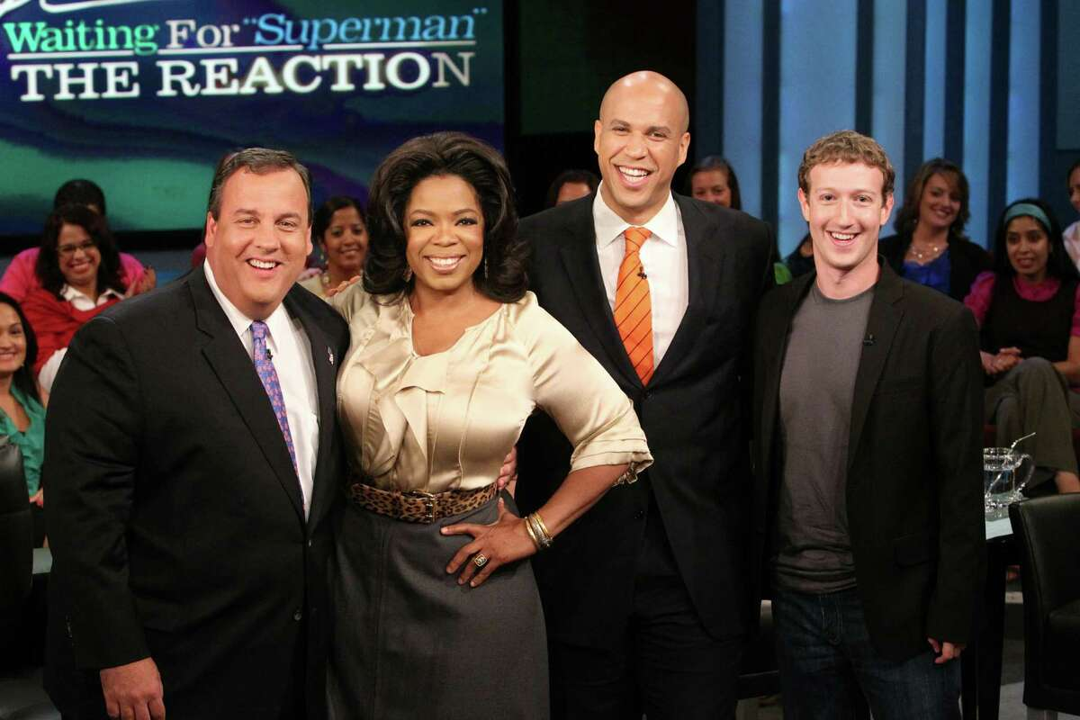 In this handout photo provided by Harpo Productions Inc., from left, then-New Jersey Gov. Chris Christie, Oprah Winfrey and then-Newark, N.J., Mayor Cory Booker stand with Mark Zuckerberg, founder of Facebook, after he announced on