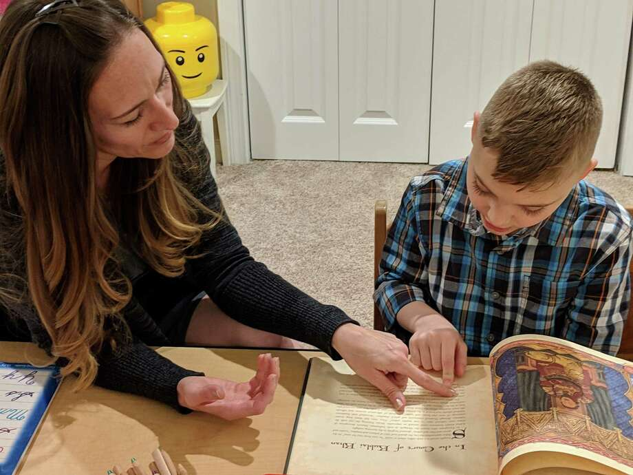 Lina Schlotter helps her son, Tucker, 10, as he reads a biography of Marco Polo. Schlotter homeschools Tucker. Photo: Kathleen Megan / CTMirror.org