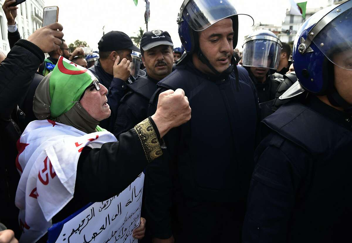 Algerian protesters gesture as members of the security forces walk away during an anti-government demonstration in the capital Algiers on April 12, 2019. - Algerian protesters gathered for the first Friday protests since the announcement of presidential elections to succeed ousted leader Abdelaziz Bouteflika fearing a ploy by the ruling system to stay in power. (Photo by RYAD KRAMDI / AFP)RYAD KRAMDI/AFP/Getty Images