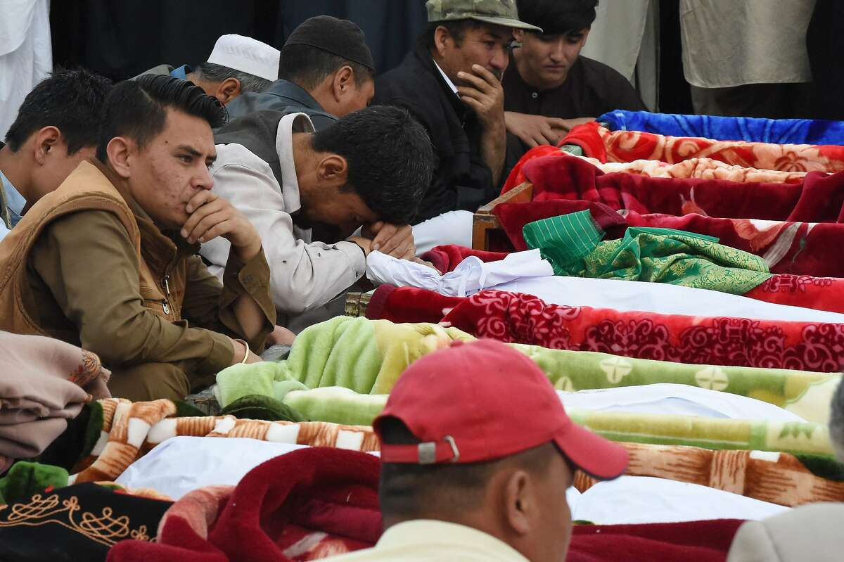 Pakistani mourners of the Shia Hazara ethnic minority sit next the bodies of blast victims during their funeral in Quetta on April 12, 2019, following a suicide attack at a crowded fruit market. - At least 20 people were killed and 48 wounded on April 12 by a powerful suicide blast apparently targeting the Shia Hazara ethnic minority at a crowded fruit market in Pakistan's Quetta city, officials said. (Photo by BANARAS KHAN / AFP)BANARAS KHAN/AFP/Getty Images