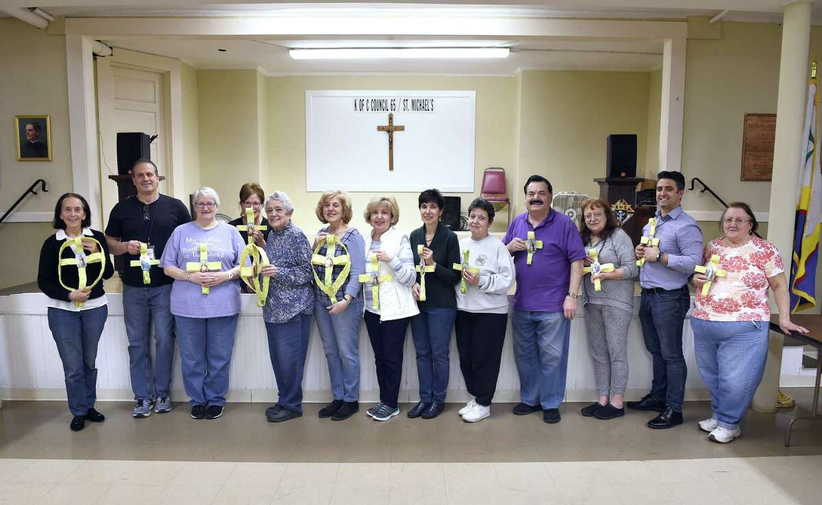 Jean Quartiano (far left) and a group of volunteers that make palm crosses in the basement of St. Michael Church in New Haven on April 11, 2019. This is the third year that volunteers under the direction of Jean Quartiano have made palm crosses for parishioners of the church for Palm Sunday.
