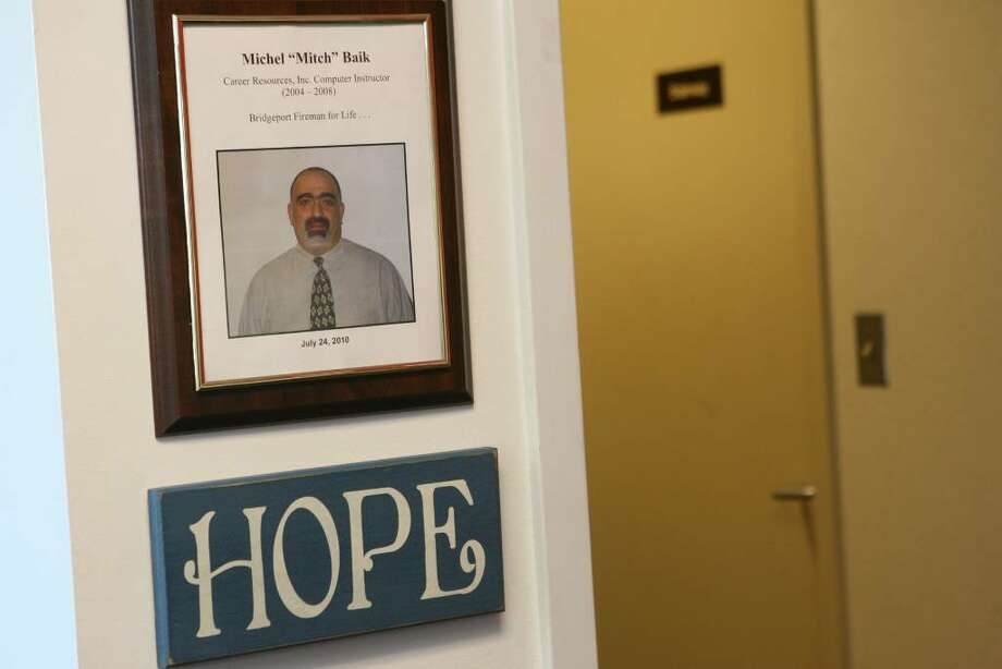 A picture of Michel Baik hangs on a wall The Workplace, Inc. where he worked before becoming a firefighter. Baik died while fighting a fire on July 24, 2010. Photo: B.K. Angeletti / Connecticut Post
