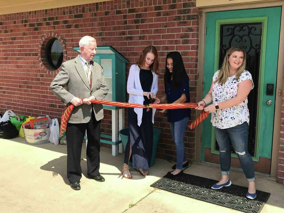 Pearland Mayor Tom Reid, left, and Dr. Kirra Randolph join Pearland Junior High West seventh-graders Katey Norman and Ariana Perez at a ceremony to open the Free Little Pantry at Embrace Wellness and Chiropractic, 4229 Wells Drive. Perez and Norman created the pantry — stocked with nonperishable and hygiene items for those in need — out of a concern to do something to help homeless people.