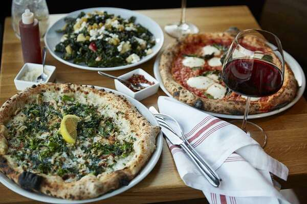 A clam pie with broccoli rabe (left) and a margherita pie are two creations by chef Tim LaBant, owner of the newly opened Parlor.
