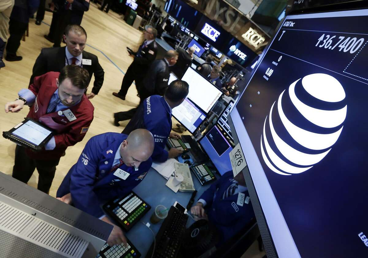 FILE - In this Monday, May 19, 2014, file photo, traders gather at the post that handles AT&T on the floor of the New York Stock Exchange. Online-cable providers like YouTube TV, DirecTV Now and Hulu with Live TV lured users with digital