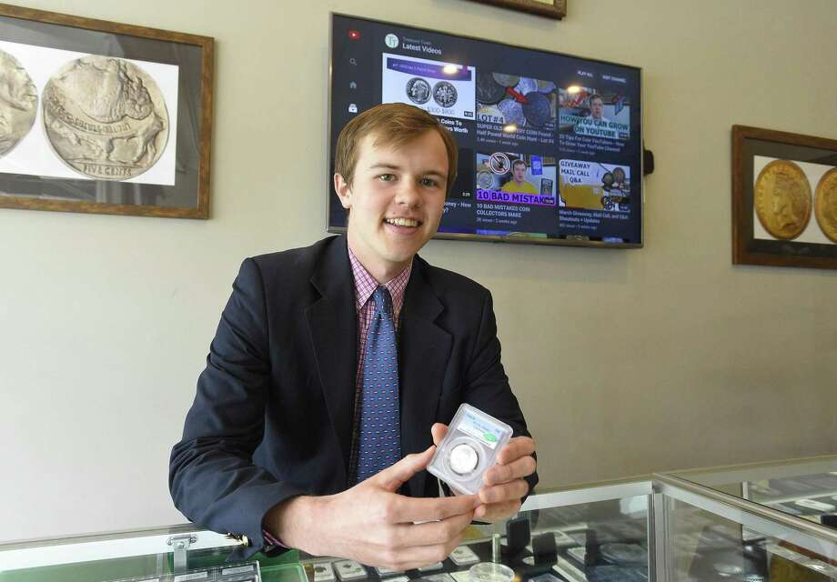 Christian Hartcher, an avid coin collector who has a YouTube following of 18,000 subscribers, is photograph Thursday, April 11, 2019 at his place of employment, Happy Coins in Greenwich, Connecticut. Hartcher is holding a rare 1936 D Cincinnati Commemorative Silver Half Dollar coin, that was recently sold to a private collector. Photo: Matthew Brown / Hearst Connecticut Media / Stamford Advocate