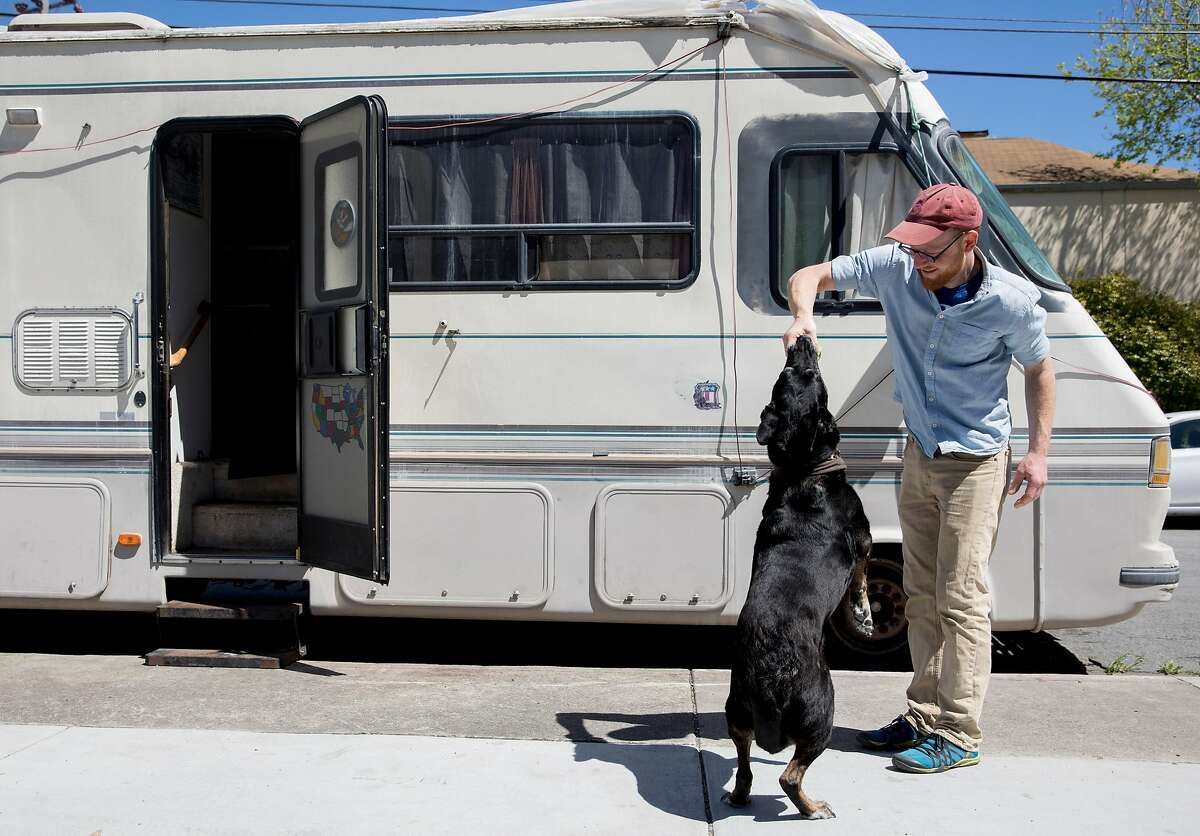 Paul Kastner plays with his dog Bandit outside of the RV he lives in while parked along 8th Street in Berkeley, Calif. Tuesday, April 9, 2019.