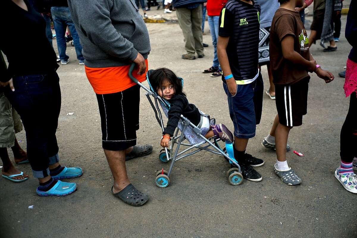 A young migrant who traveled with a caravan of Central Americans rests in her baby stroller as she and others line up for a free lunch outside the Benito Juarez Sports Center that is serving as a shelter for migrants in Tijuana, Mexico, Wednesday, Nov. 28, 2018. As Mexico wrestles with what to do with more than 5,000 Central American migrants camped out at a sports complex in the border city of Tijuana, President-elect Andres Manuel Lopez Obrador's government signaled it would be willing to house the migrants on Mexican soil while they apply for asylum in the United States � a key demand of U.S. President Donald Trump. (AP Photo/Ramon Espinosa)