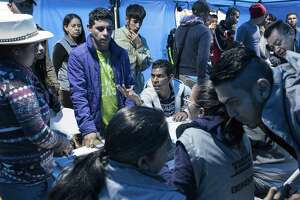 Venezuelan migrants are registered as they arrive at a new refugee center in Bogota, Colombia, in November. The exodus of Venezuelans from their once-properous but now poverty-stricken nation is a major humanitarian crisis.