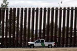 A U.S. Customs and Border Protection vehicle sits near the wall in April as President Donald Trump visits a new section of the border wall with Mexico in Calexico. The president's immigration stances are full of contradictions.