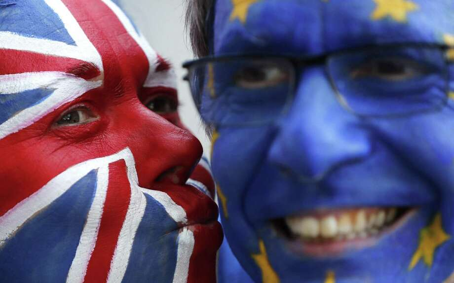 Activists pose March 21 with their faces painted in the EU and Union Flag colors during an anti-Brexit campaign stunt outside EU headquarters during an EU summit in Brussels. The country's struggle to leave the European Union is one of the great political crisis to afflict Britain in the postwar period. Photo: Frank Augstein /Associated Press / Copyright 2019 The Associated Press. All rights reserved