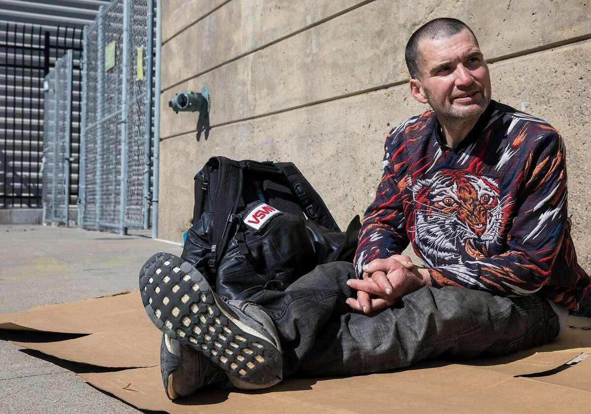 Tyson Feilzer, 40, sits on a cardboard box along Bryant Street near Main Street along the Embarcadero in San Francisco, Calif. Sunday, April 7, 2019.