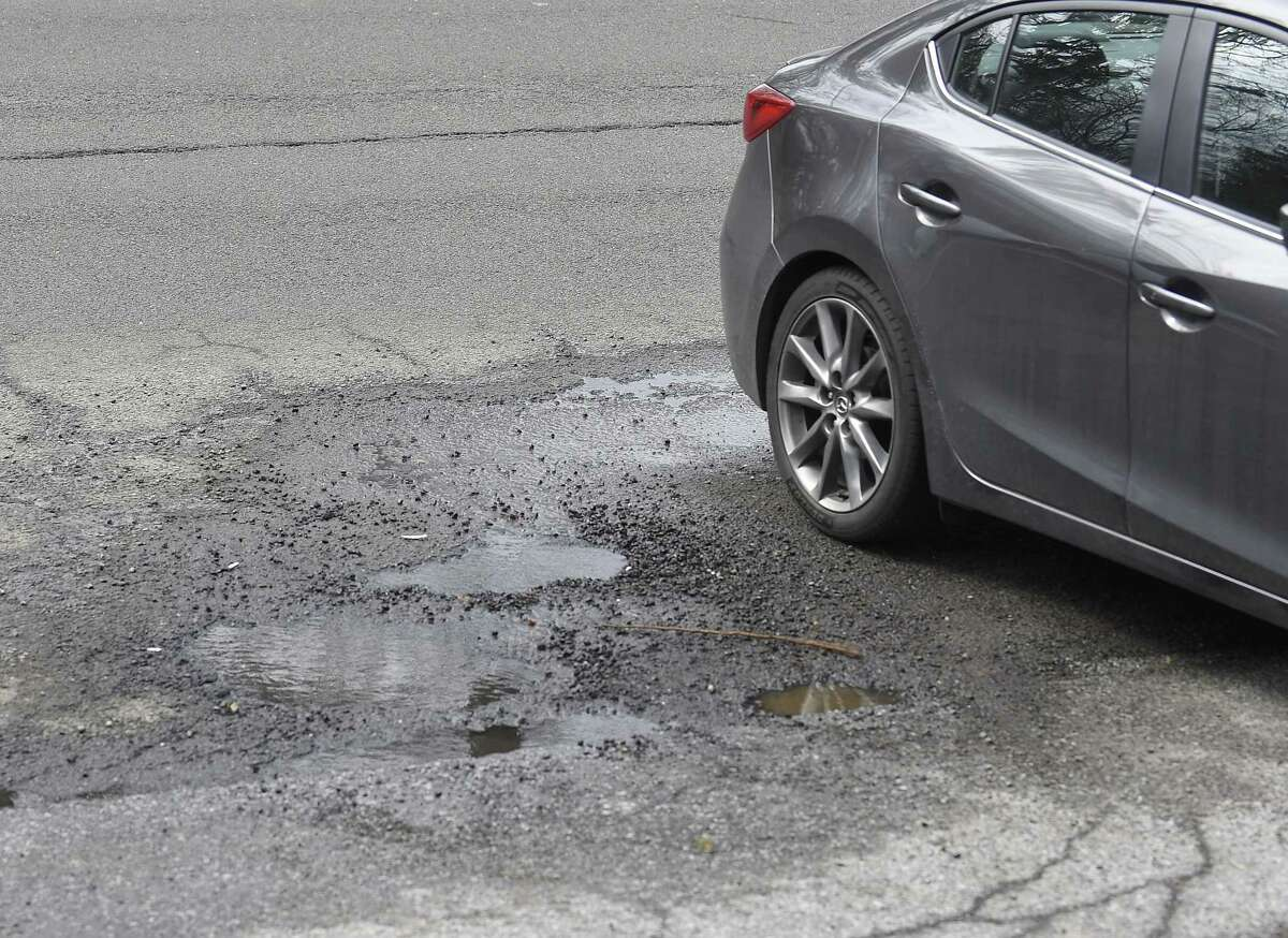 A car passes by a pothole at Long Ridge Road and Terrace Avenue in Stamford, Conn. on Friday, March 15, 2019.