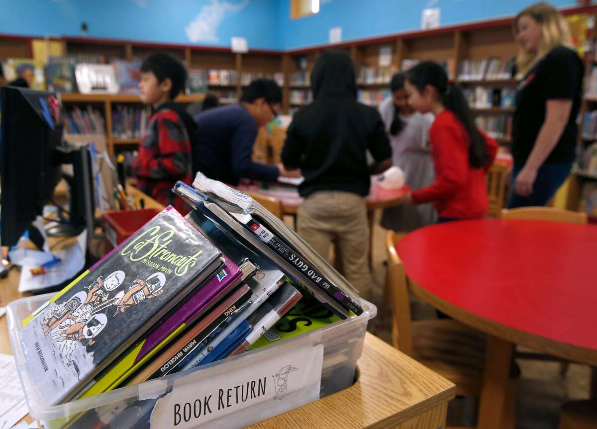 Books wait to be checked back in at the Bella Vista Elementary School library, supervised by Trish Belenson (right) in Oakland, Calif. on Wednesday, Jan. 30, 2019.
