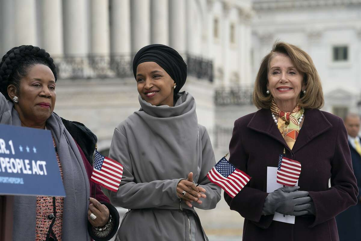 """Freshman Rep. Ilhan Omar, D-Minn., center, smiles as she stands between Rep. Sheila Jackson Lee, D-Texas, left, and Speaker of the House Nancy Pelosi, D-Calif., as Democrats rally outside the Capitol ahead of passage of H.R. 1, """"The For the People Act,"""" a bill which aims to expand voting rights and strengthen ethics rules, in Washington, Friday, March 8, 2019. House Democrats are rounding the first 100 days of their new majority taking stock of their accomplishments, noting the stumbles and marking their place as a frontline of resistance to President Donald Trump. (AP Photo/J. Scott Applewhite)"""