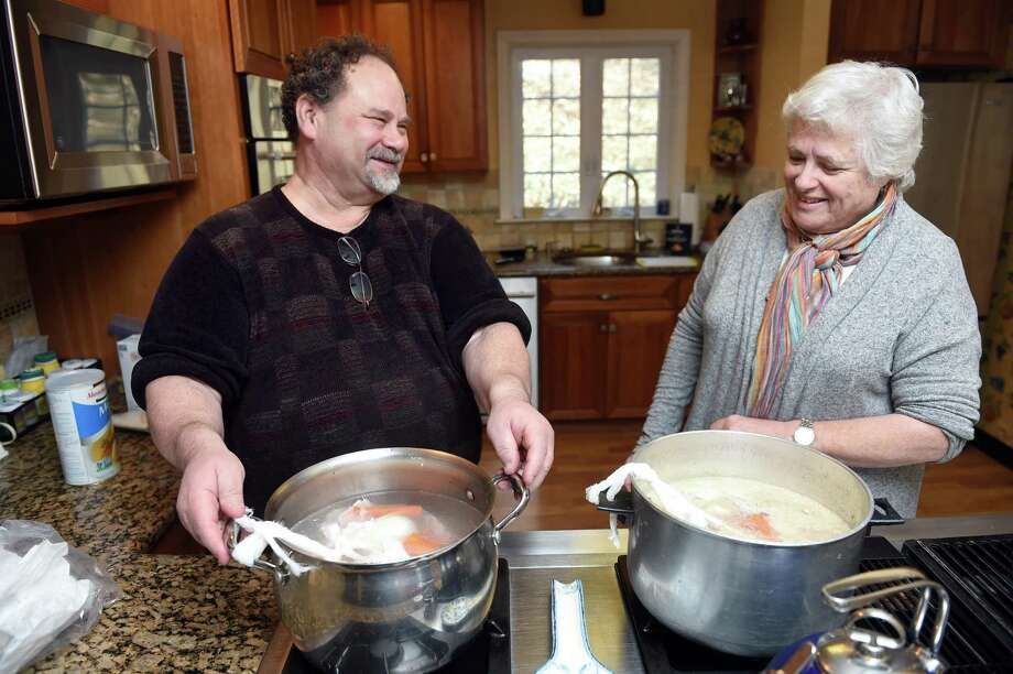 New Haven Register reporter Mark Zaretsky (left) places a pot of fish stock on the cooktop in Judy Zellman Sklarz's home in New Haven to use to make gefilte fish on March 14, 2019. Photo: Arnold Gold / Hearst Connecticut Media / New Haven Register