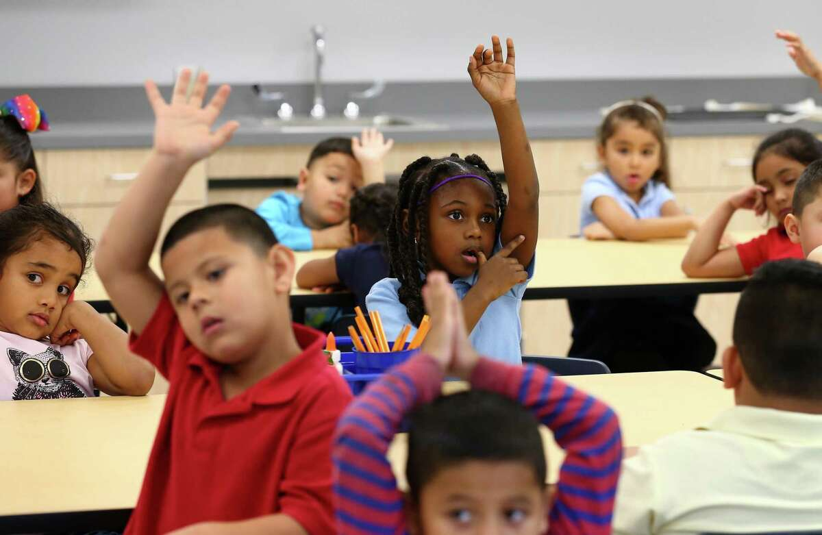 Kindergarteners raise their hands Mrs. Jackson tried to establish silence in her art classroom at Robinson Elementary Monday, Jan. 8, 2018, in Houston. Students returned to their home campus after it was flooded during Hurricane Harvey. Students were bused to Holland Middle School and Pleasantville Elementary during that time. The school is the first of seven severely flood-damaged HISD schools to reopen since the storm. ( Godofredo A. Vasquez / Houston Chronicle )