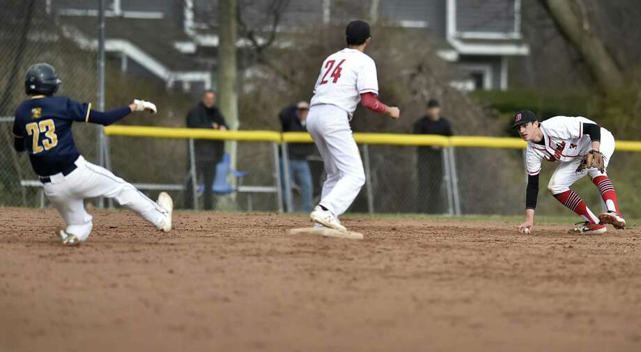 East Haven's Giro Esposito slides into second base as Anthony Burzynski of Branford, center, waits for a throw from teammate Jake Bodner on Friday. Photo: Peter Hvizdak / Hearst Connecticut Media / New Haven Register