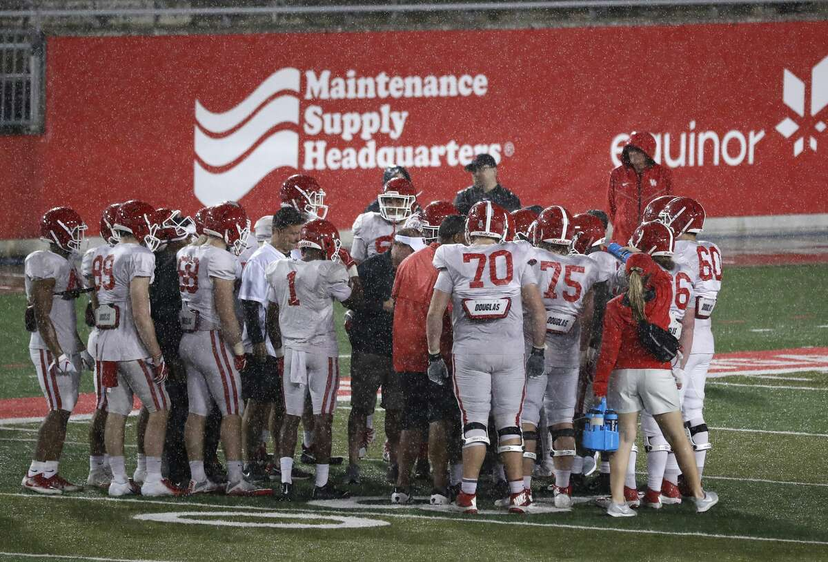 """The Houston Cougars offense huddles as the rain drenched them during the University of Houston's """"Friday night lights"""" spring football practice, Friday, April 12, 2019, in Houston."""